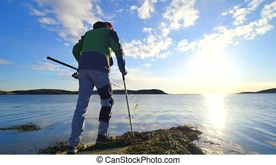 Fisherman with medicine crutch and broken leg fixed in immobilizer is fishing. Hurt man put crutch into jacket pocket and throws pushing bait with flexible fishing rod far into the sea.