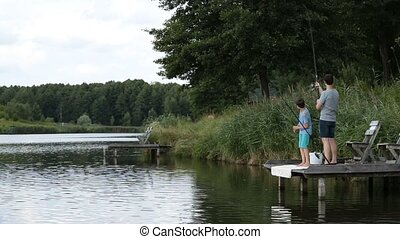 Fisherman with spinning rod catching fish on lake - Hipster...