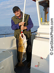Fisherman with very big fish on the boat