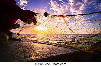 Fisherman's hand silhouette  throwing fishing net at sunset, Crete, Greece