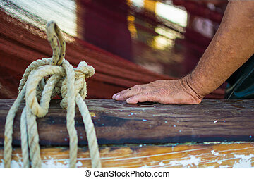 Fisherman`s Hand With Fishing Net in the Background. Wet and Wrinkled Hand Leaning on a Wooden Boat Fence. Fisherman`s Hand Next to Tied Rope.