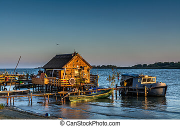 Fisherman's House, the old dock and the boat on the lake. Rustic landscape with wooden pier in the summer evening.