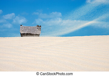 Fisherman's hut on the beach with sandstorm and blue sky.