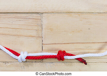 fisherman's knot made with red rope on wooden background.