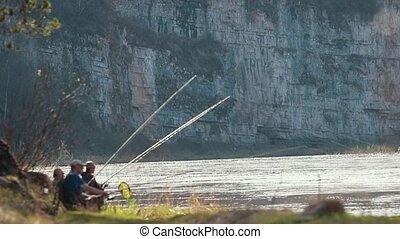 Fishermans sitting near the river holding a rod and waiting...