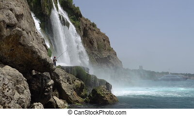 Fishermans under the Spray of Picturesque Lower Duden Waterfall Falling into the Sea in Antalya, Turkey.