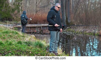 Fishermans with fishing rods near the river in morning