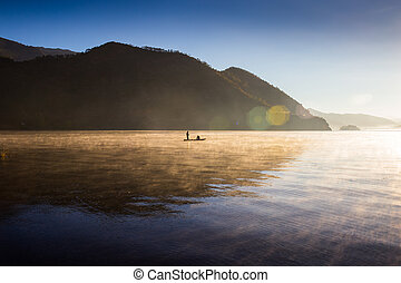 Fishermen at dawn on the mountain lake in a boat