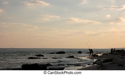 Fishermen catch fish with enthusiasm at the seaside.