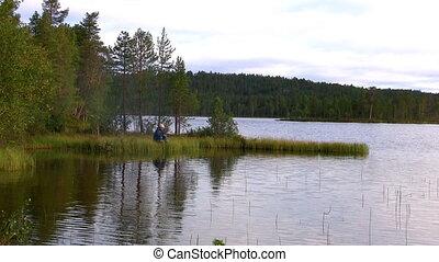 fishermen fishing on lake, norway