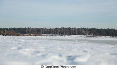 Fishermen go on snow-covered ice.