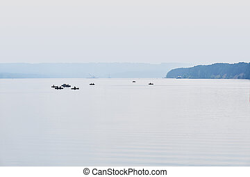 fishermen in inflatable boats fish on a wide river in the morning fog