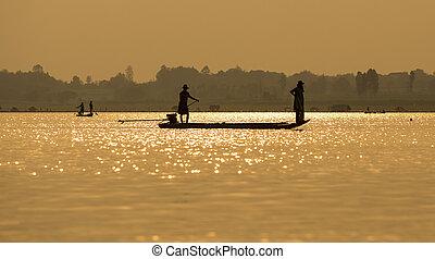 Fishermen in the boat sunrise