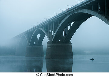 Fishermen on a boat sails under the bridge in the fog