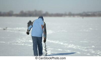 Fishermen on ice on a frozen lake near the city park -...