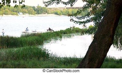 Fishermen on lake. City lake landscape background.