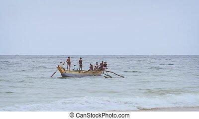 HIKKADUWA, SRI LANKA - DEC 2016: Fishermen paddling an outrigger canoe to lay nets off Hikkaduwa