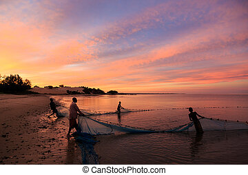 Fishermen pulling in a net from the beach at sunset