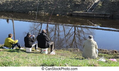 fishermen stream fishing - four fishermen sitting by the...