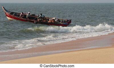 fishermen unload fresh catch of fish on beach - Kerala India