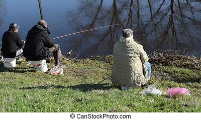 fishermen waiting bite - three fishermen patiently sitting...