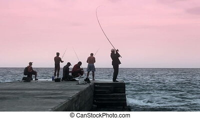 Fishermens on the pier in the sea timelapse (Full HD)
