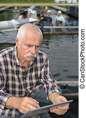 fishery businessman holding a tablet