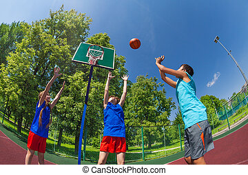 Fisheye view of children jumping for flying ball during...