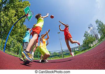 Fisheye view of teenagers playing basketball game together...