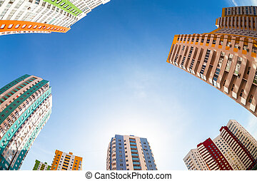 Fisheye view on the new tall apartment buildings against blue sky background
