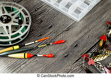 fishig reel, iron baits and bobbers at grey wooden table