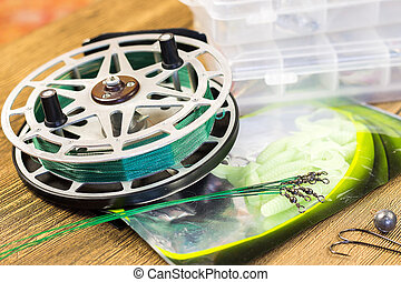 fishin acsessories and reel on the wooden table - fishin...