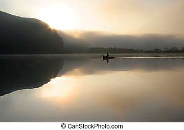 Fishing - A lone fisherman on a tranquil and misty lake with...