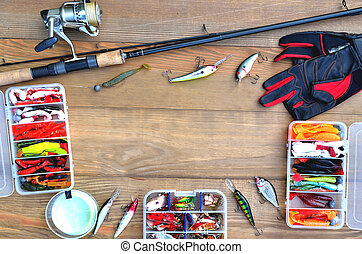 fishing accessories fishing rod, reel with fishing line, silicone baits and lures, spinning gloves and accessory box on a wooden background, copy space flat lay