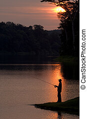 Fishing At Sunset - A silhouette of a fisherman as the sun...