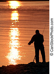 Fishing at Sunset - The silhouette of a man fishing at...