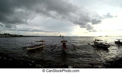 Fishing boat anchored on sea shore at twilight dusk sunset....