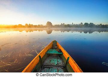 Fishing boat at foggy sunrise on a lake