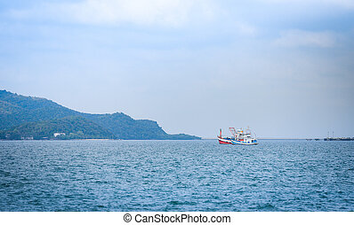 fishing boat at harbor in the ocean sea and mountain background at Thai Bay