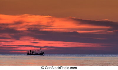 Fishing Boat at Skyline Red Clouds in Dark Sky after Sunset