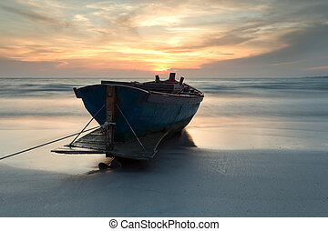 Fishing boat at the beach during sunset