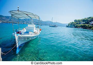 Fishing boat docked to coast on the beach, Greece.