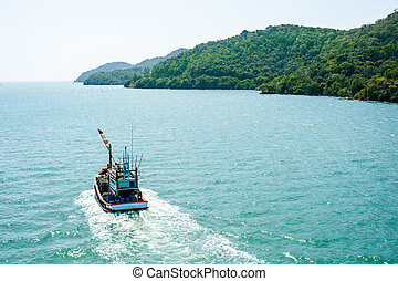 Fishing boat floating on the water blue sea and sky