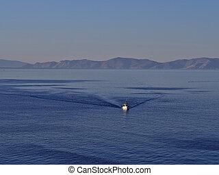Fishing boat in calm blue sea.