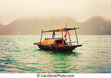 Fishing boat in Ha Long Bay Vietnam at sunset