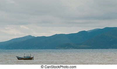 Fishing boat in sea. Vietnam. Against the backdrop of the mountains.