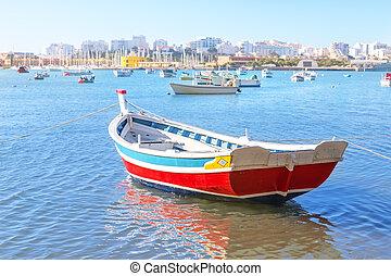 Fishing boat in the bay of Ferragudo village summer. ...