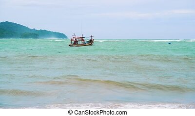fishing boat in the open sea, strong waves and a wind storm