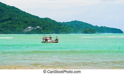 fishing boat in the sea on the waves, tropical island