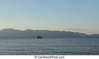 Fishing boat is crossing over calm sea